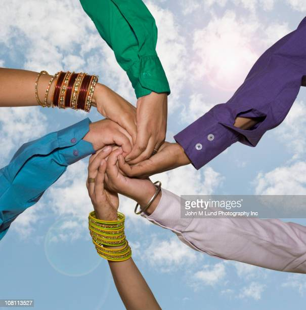 People holding hands together against blue sky