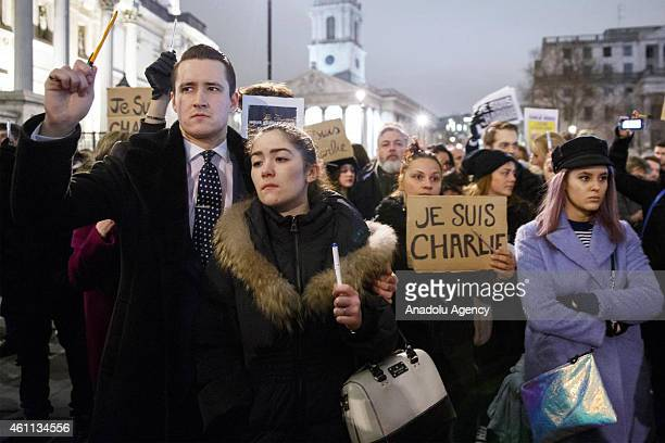 People holding pens as they attend to a silent vigil in Trafalgar Square London England to condemn the gun attack at French satirical magazine...