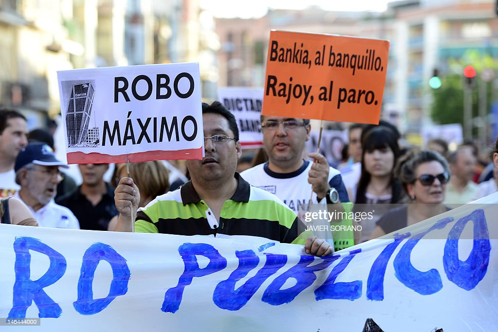 People holding placards reading 'Maximum theft' and 'Bankia to the bench trail. Rajoy, unemployed' during a demonstration against bank fraud on June 16, 2012 in Madrid. Spain's 'indignant' activists filed a criminal complaint on June 14, 2012 against the former management of Bankia, whose partial nationalisation helped push Madrid to seek a massive EU bailout. Last month, Bankia revised its 2011 results from a net profit of 309 million euros ($387 million) to a loss of nearly three billion euros and asked the state for a bailout of 19 billion euros, the largest in Spanish history. AFP PHOTO / JAVIER SORIANO