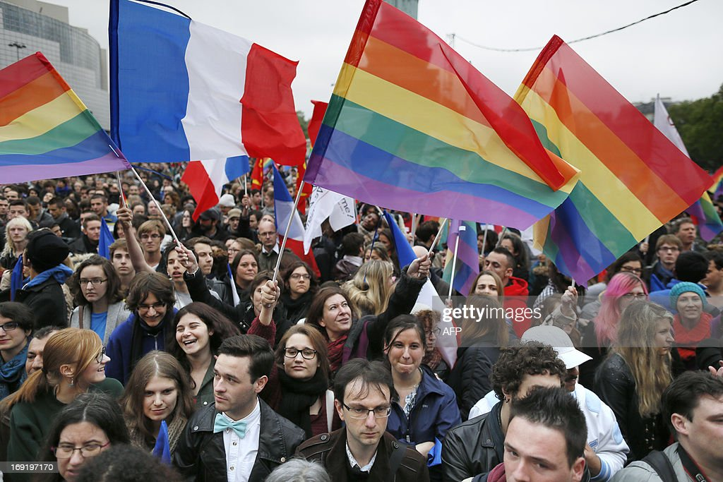 People holding rainbow flags attend the event 'Concert pour tous!' (Concert for all!) on May 21, 2013 at the Bastille square in Paris. The 'Concert for all!' in reference of the French anti-gay marriage movement 'Manif pour tous !' (Demonstration for all!), is held to celebrate the legalisation of same-sex marriage. After months of acrimonious debate and hundreds of protests that have occasionally spilled over into violence, France's National Assembly approved on April 23, 2013 a bill making the country the 14th to legalise same-sex marriage.