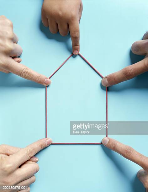 People holding rubber band in geometric shape, overhead view
