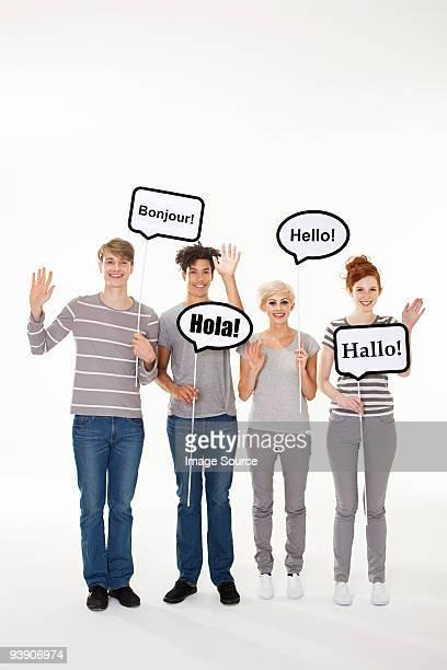 Les gens tenant les panneaux indiquant Bonjour dans différentes langues