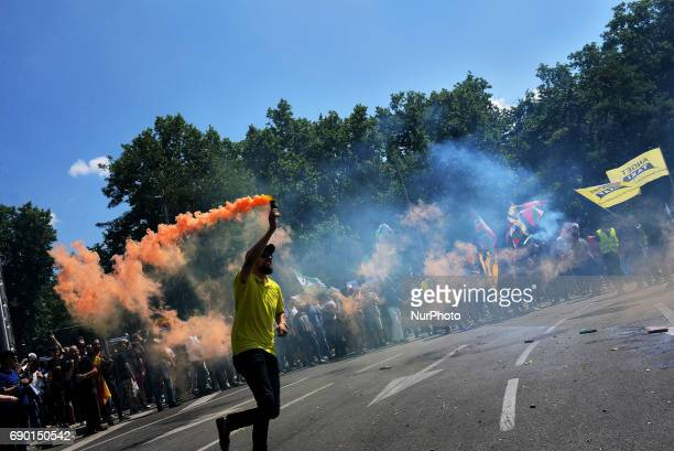 People holding smoke bombs march during a protest by a Spanish taxi drivers in Madrid on 30 th May 2017