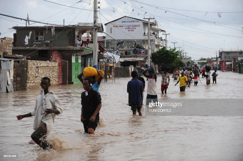 People holding some of their belongings walks during a massive exodus of the flooded city of Gonaives some 200 kilometres north of Port Au Prince on...