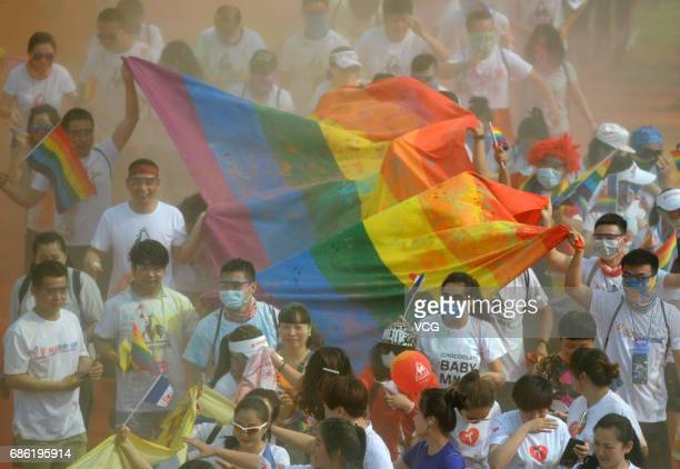 People holding the rainbow flag participate in the color run on May 21 2017 in Taiyuan Shanxi Province of China Around 300 people including about 20...
