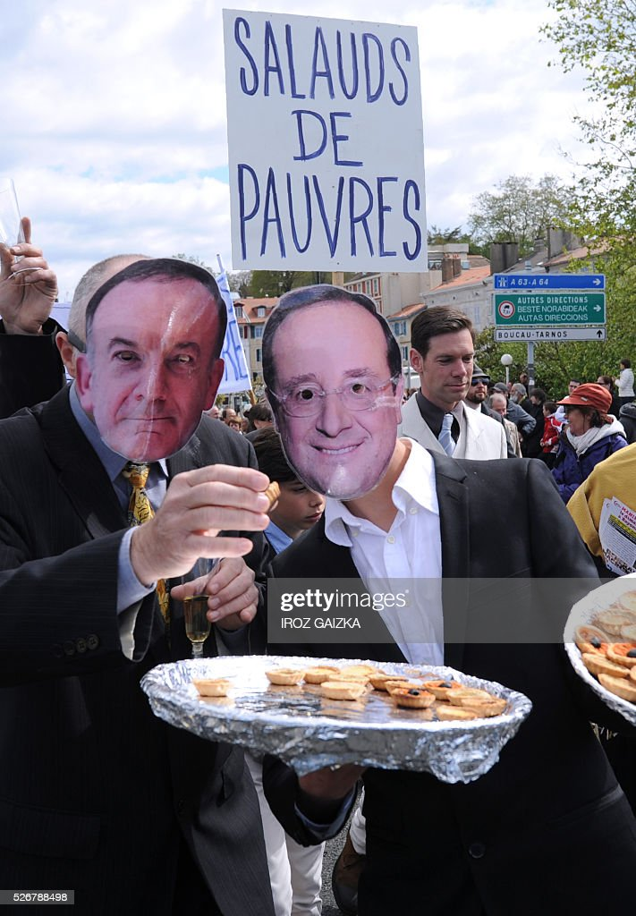 People holding trays of appetisers wear masks of the head of French employers' association MEDEF Pierre Gattaz (L) and French President Francois Hollande as members of the movement 'Bizi !' ('live' in Basque) stage a 'Rich peoples protest' to mark May Day in Bayonne on May 1, 2016. / AFP / IROZ