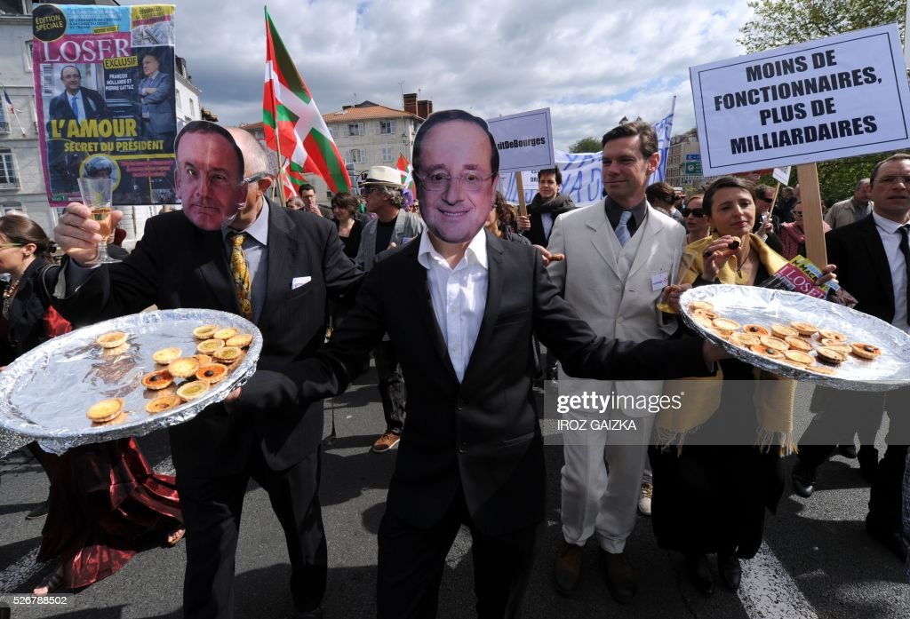 TOPSHOT People holding trays of appetisers wear masks of the head of French employers' association MEDEF Pierre Gattaz and French President Francois...