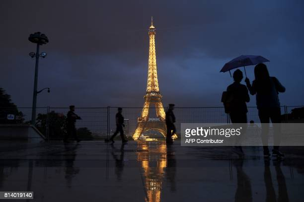 People holding umbrellas and gendarmes walk at the Palais de Chaillot near the Eiffel Tower in Paris on July 13 as US President Donald Trump and...