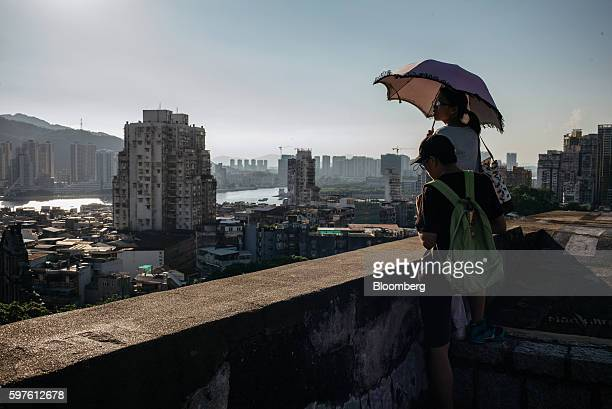 People holding umbrellas look out as buildings stand in Macau China on Sunday July 22 2016 Macau is scheduled to release gross domestic product...