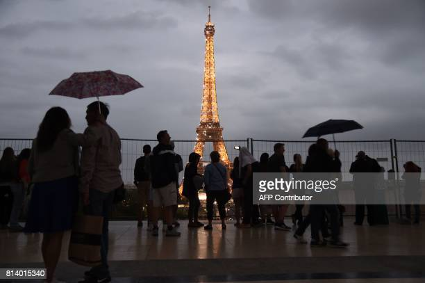 People holding umbrellas look towards the Eiffel Tower in Paris on July 13 as US President Donald Trump and French President Emmanuel Macron attend a...