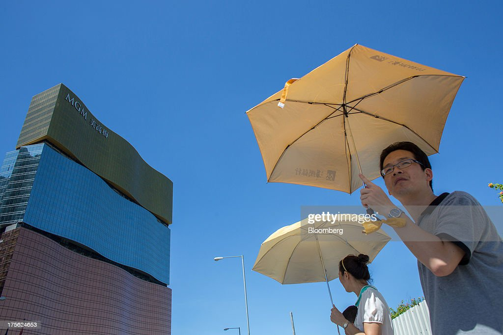People holding umbrellas stand outside the MGM Macau, operated by MGM China Holdings Ltd., in Macau, China, on Sunday, Aug. 4, 2013. MGM China Holdings is scheduled to release second quarter results on Aug. 6. Photographer: Lam Yik Fei/Bloomberg via Getty Images