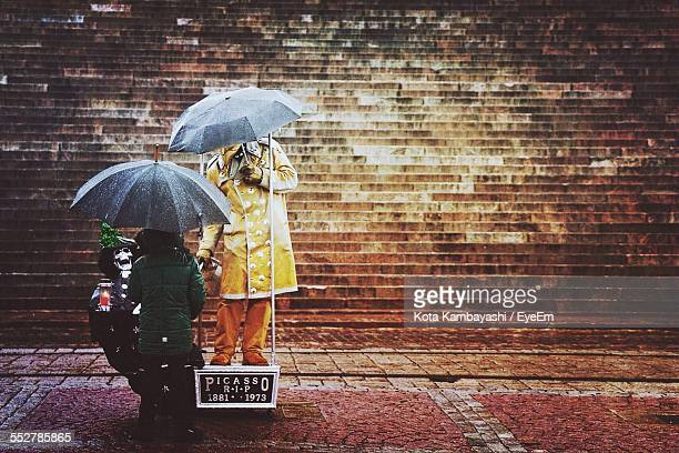 People Holding Umbrellas While Standing On Footpath During Rainy Season