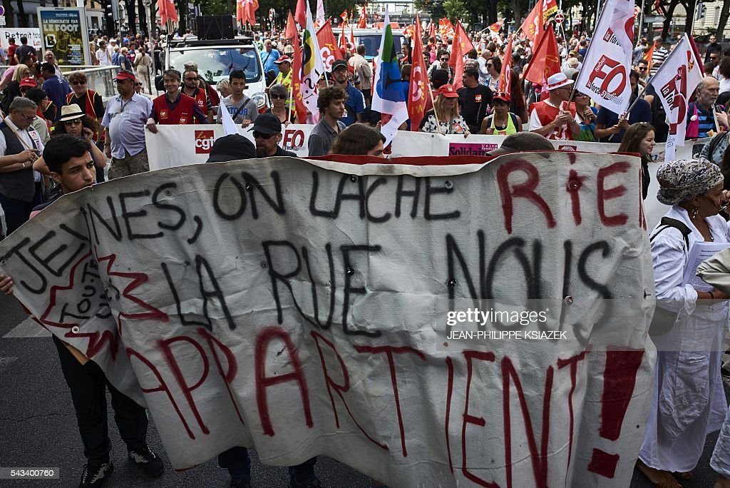 People holds a banner reading 'Youth, we give nothing away, the street belongs to us' during a demonstration against controversial labour reforms, on June 28, 2016 in Lyon. Unions have called repeated strikes and marches in opposition to the law, which seeks to bring down France's intractable 10-percent unemployment rate by making it easier to hire and fire workers. / AFP / JEAN