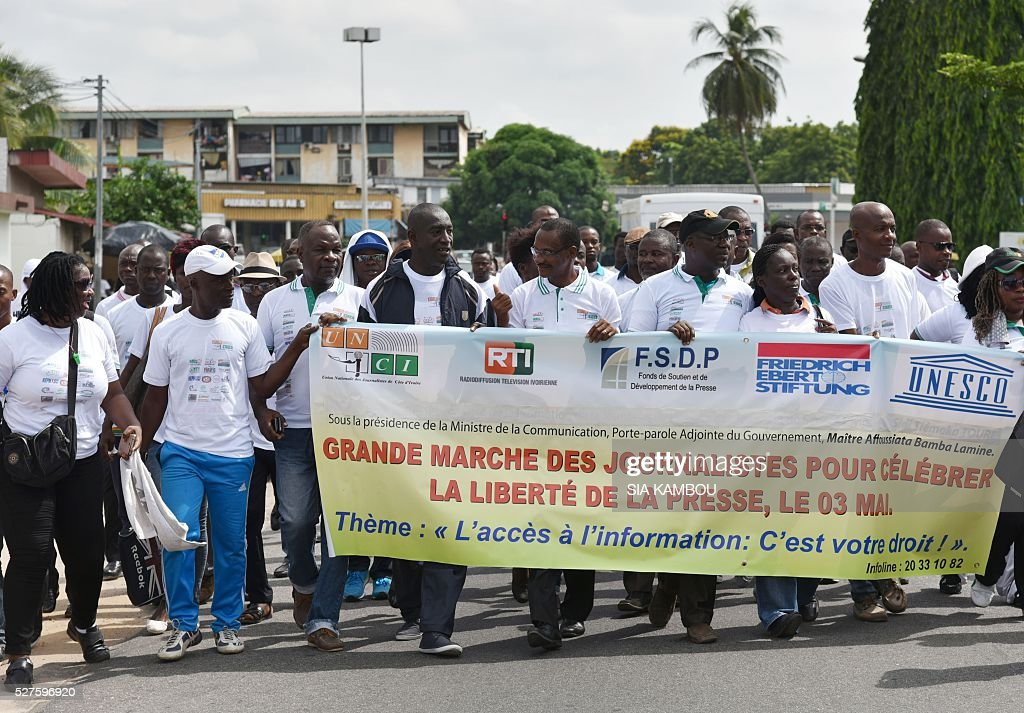 People holds a banner which translates as 'Journalists march to celebrates the press freedom on May 3' during a march in Abidjan on May 3, 2016 for the World Press Freedom day. / AFP / Sia KAMBOU