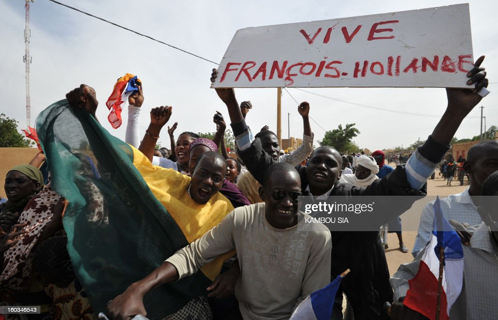 People holds a sign reading 'Long live Francois Hollande' on January 29, 2013 in Ansongo, a town south of the northern Malian city of Gao, as Niger troops enter the city. Troops from Niger and Mali on January 29 entered Ansongo, which along with Gao was recaptured by French-led soldiers over the weekend in a lightning offensive against radicals holding Mali's north. So far, just 2,000 African troops have been sent to Mali or neighboring Niger, many of them from Chad, to boost the French-led offensive which began on January 11 and led to the recapture of several towns, including Ansongo. AFP PHOTO / KAMBOU SIA