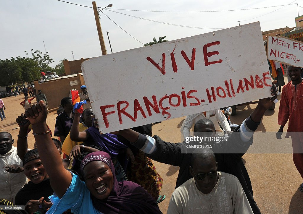 People holds a sign reading 'Long live Francois Hollande' on January 29, 2013 in Ansongo, a town south of the northern Malian city of Gao, as Niger troops enter the city. Troops from Niger and Mali on January 29 entered Ansongo, which along with Gao was recaptured by French-led soldiers over the weekend in a lightning offensive against radicals holding Mali's north. So far, just 2,000 African troops have been sent to Mali or neighboring Niger, many of them from Chad, to boost the French-led offensive which began on January 11 and led to the recapture of several towns, including Ansongo.