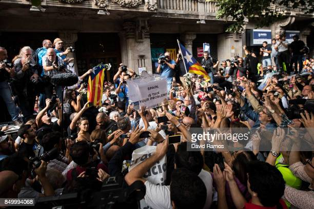 People holds up a ballot box which says 'Spain is this your problem' outside the Catalan VicePresident and Economy office as police officers holds a...