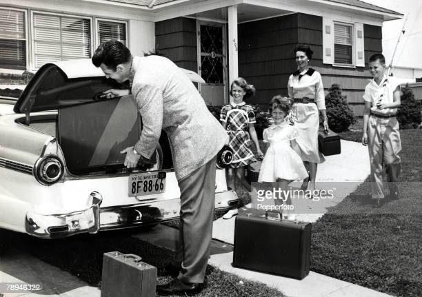 circa 1950's An American family excited as they leave for their vacation as the father loads the luggage into the car