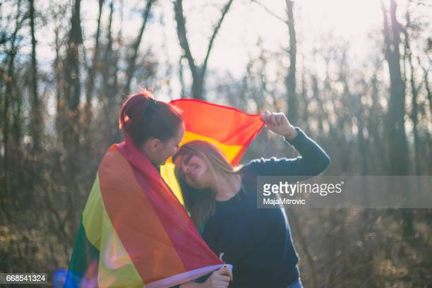 people, homosexuality, gay and love concept - close up of happy lesbian couple holding hands over rainbow flag