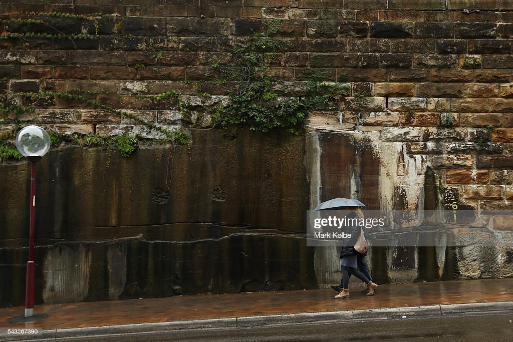 People huddle under an umbrella as they walk near the Sydney Opera House on June 27, 2016 in Sydney, Australia. Sydney experienced its coldest day of the year on Sunday, and more icy weather is forecast for later in the week when a second cold front hits later in the week.