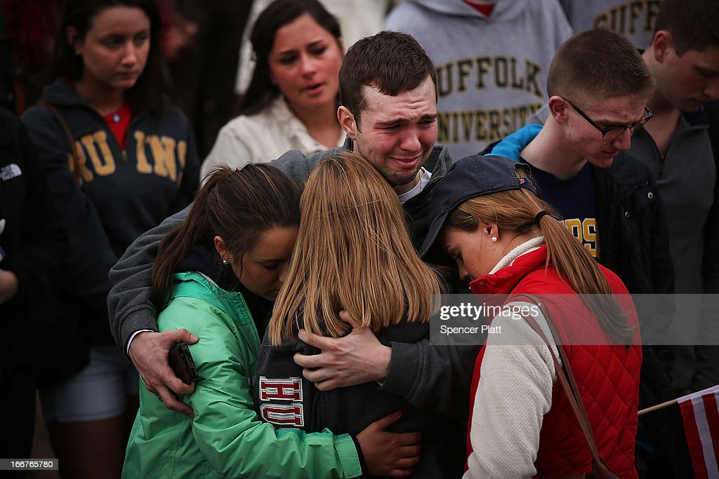 People hug and cry during a vigil for victims of the Boston Marathon bombings at Boston Commons on April 16, 2013 in Boston, Massachusetts. The twin bombings, which occurred near the marathon finish line, resulted in the deaths of three people while hospitalizing at least 140. The bombings at the 116-year-old Boston race, resulted in heightened security across the nation with cancellations of many professional sporting events as authorities search for a motive to the violence.