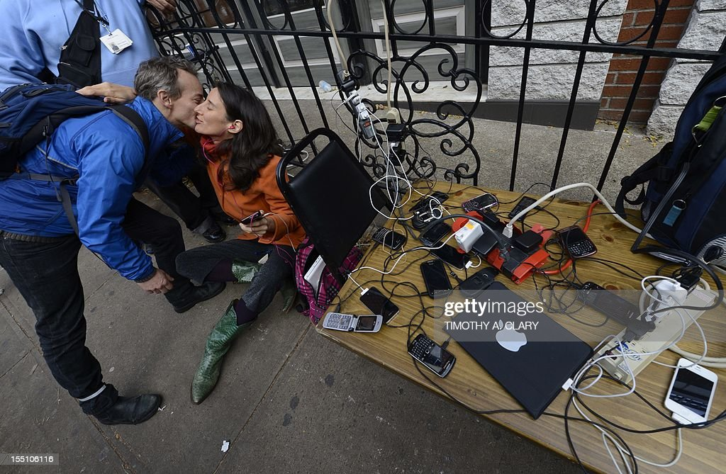 People hug as they wait to have phones and laptops charged off a generation set up in the West Village November 1, 2012 as New Yorkers cope with the aftermath of Hurricane Sandy. The storm left large parts of York City without power and transportation. The