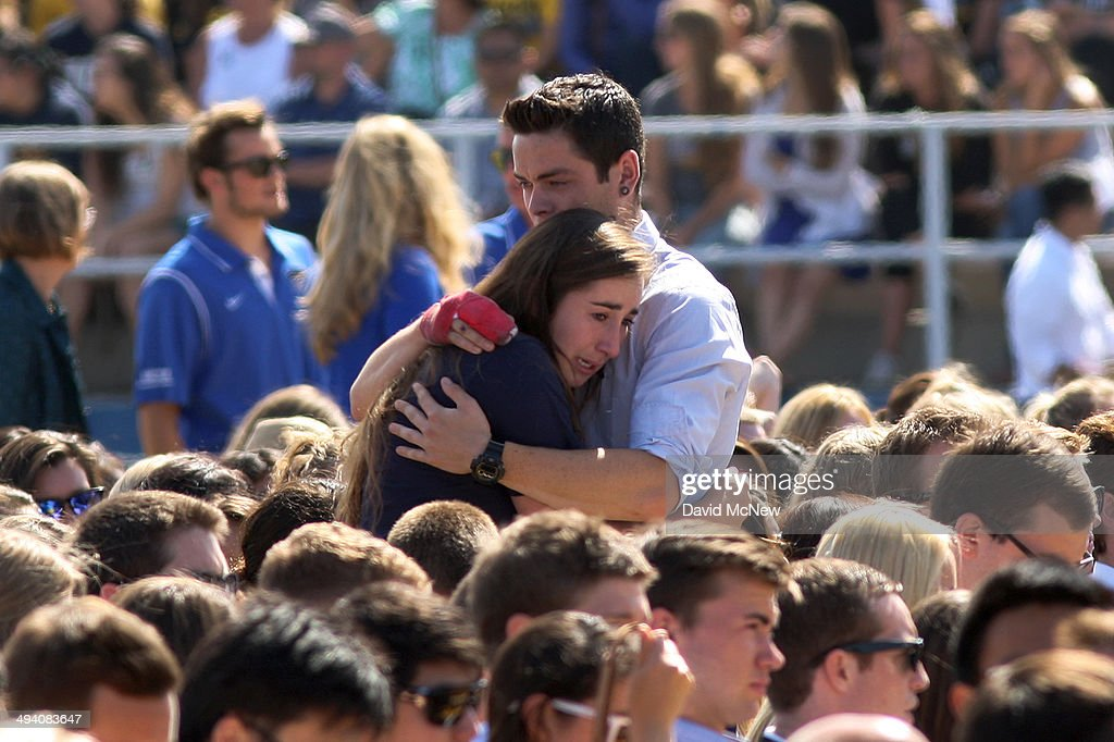 People hug at a public memorial on the Day of Mourning and Reflection for the victims of a killing spree at University of California, Santa Barbara on May 27, 2014 in Isla Vista, California. Elliot Rodger killed six college students at the start of Memorial Day weekend and wounded seven other people, stabbing three then shooting and running people down in his BMW near UCSB before shooting himself in the head as he drove. Police officers found three legally-purchased guns registered to him inside the vehicle. Prior to the murders, Rodger posted YouTube videos declaring his intention to annihilate the girls who rejected him sexually and others in retaliation for his remaining a virgin at age 22.
