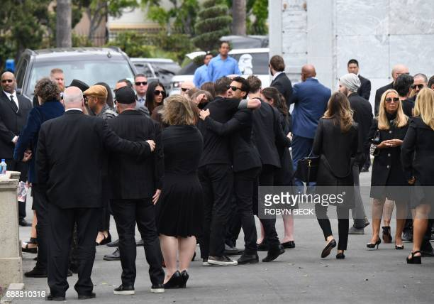 People hug at the funeral and memorial service for Soundgarden frontman Chris Cornell May 26 2017 at Hollywood Forever Cemetery in Los Angeles...