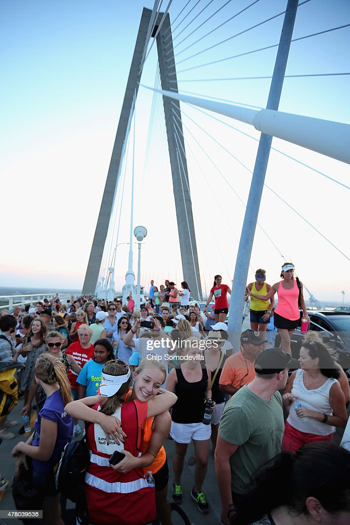 People hug, cheer and sing together after participating in a 'unity chain' across the Arthur Ravenel Jr. Bridge over the Cooper River June 21, 2015 in Charleston, South Carolina. The march was organized to commemorate the nine people shot to death last Wednesday at the Emanuel African Methodist Episcopal Church by a 21-year-old white supremacist who claimed to want to start a race war.