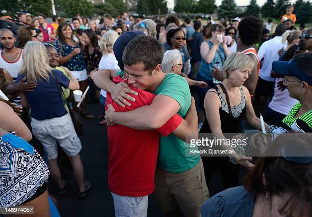 People hug during a vigil for victims at the Century 16 movie theatre where a gunmen attacked movie goers during an early morning screening of the...