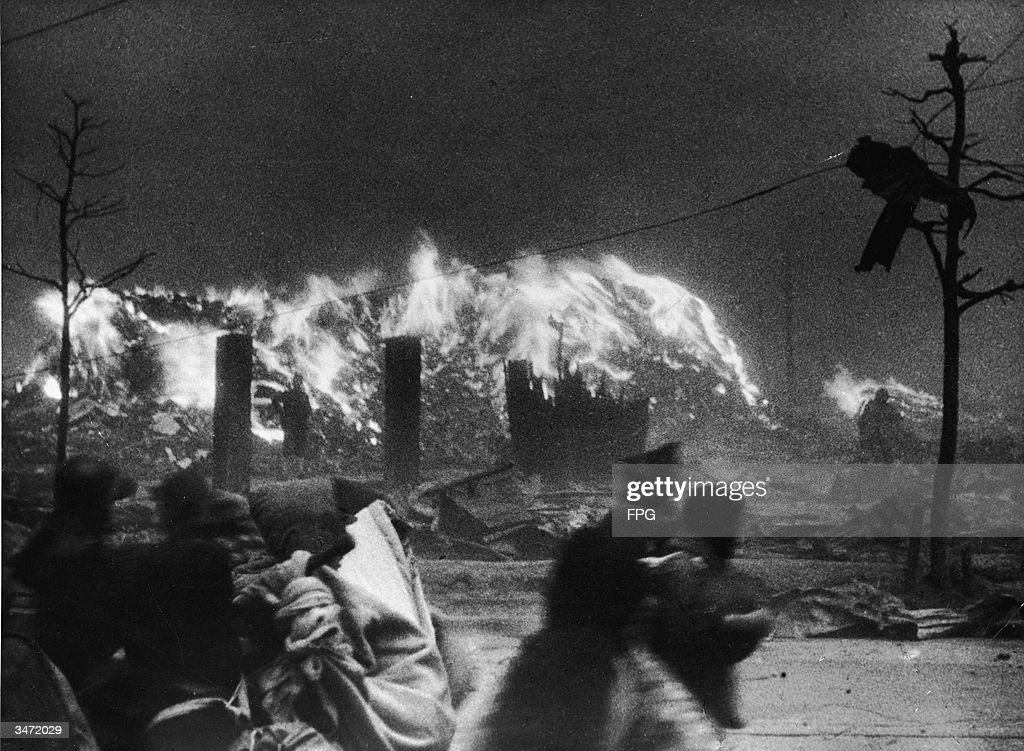 People hurry past a fire burning in the wake of an air raid, Japan, circa 1945.