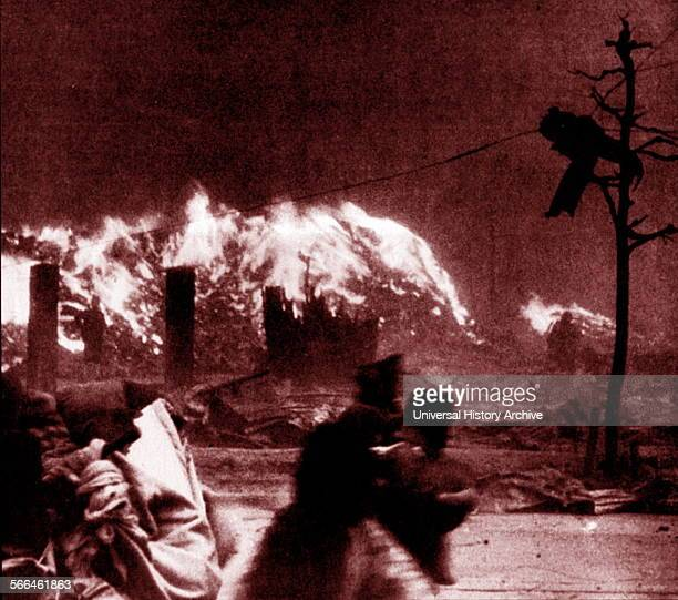 People hurry past a fire burning in the wake of an air raid Japan circa 1945