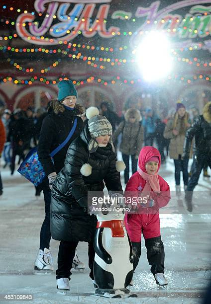 People ice skate at an ice rink on Red Square in front of historical GUM shopping mall in central Moscow on December 2 2013