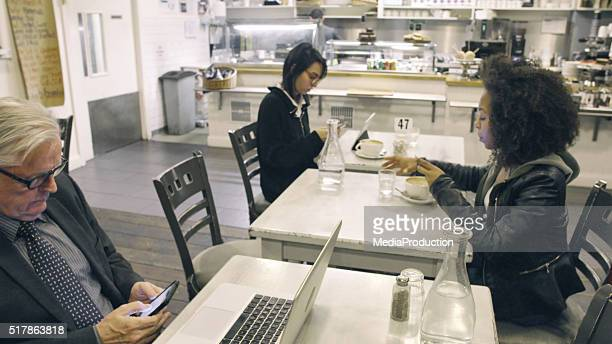 People if various ages on their phones at a cafe