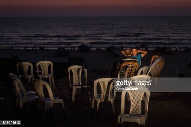 People illuminated by car headlights relax at the beach on July 21 2017 in Gaza City Gaza For the past ten years Gaza residents have lived with...