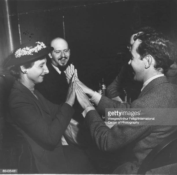 People in a bar including a woman and man touching hands and laughing and a man the editor and critic Leo Lerman wearing a suit tie and goatee in the...