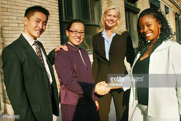 4 people in a business team shaking hands