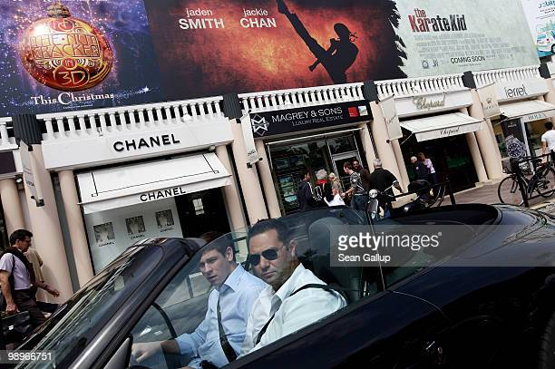People in a convertible drive past luxury stores on the Croisette prior to the annual film festival on May 11 2010 in Cannes France The 63rd Cannes...