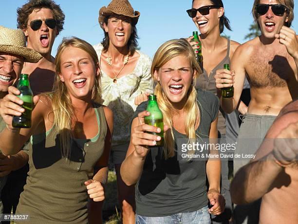 People in a field, raising their beer