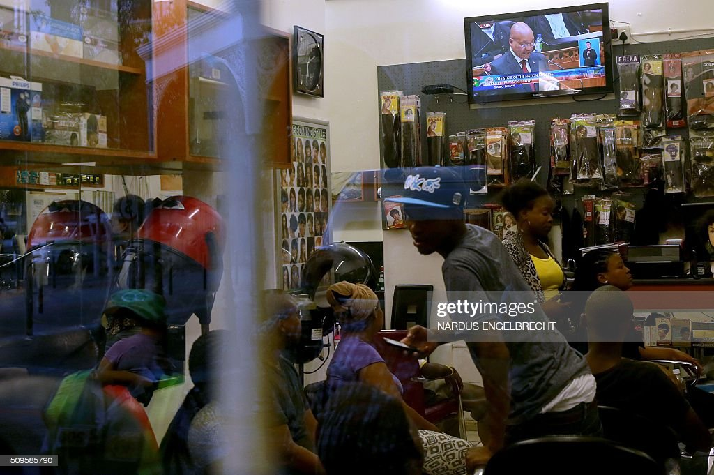 People in a hairdresser's shop watch on television President Jacob Zuma giving his State of the Nation address on February 11, 2016, in Cape Town. South African police fired stun grenades to disperse angry protesters outside parliament shortly before President Jacob Zuma was due to deliver his annual state of the nation address.The embattled president faces moves in court, in parliament and on the streets to have him impeached or dumped by the ruling African National Congress (ANC). ENGELBRECHT