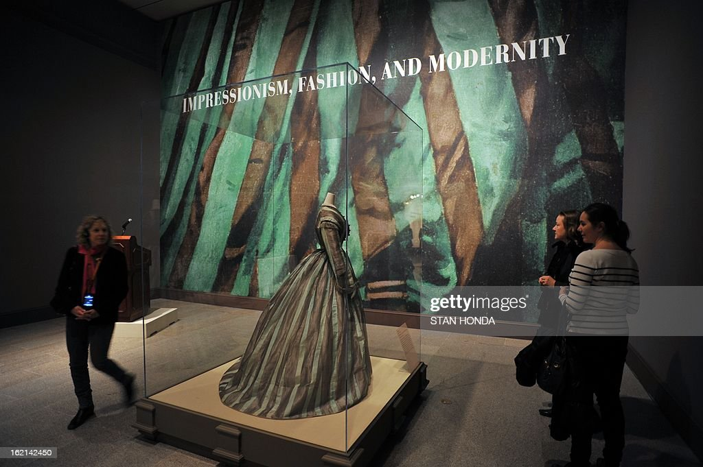 People in a media preview look at a Day Dress, British, 1865-68 at the entry to the exhibition 'Impressionism, Fashion, and Modernity' February 19, 2013 at The Metropolitan Museum of Art in New York. The look at the role of fashion in the works of the Impressionists and their contemporaries shows 80 major paintings with period costumes, accessories, fashion plates, photographs, and popular prints. AFP PHOTO/Stan HONDA