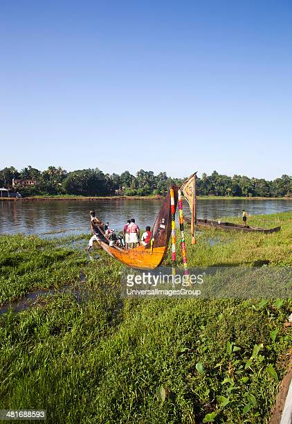 People in a snake boat at the riverside Aranmula Kerala India