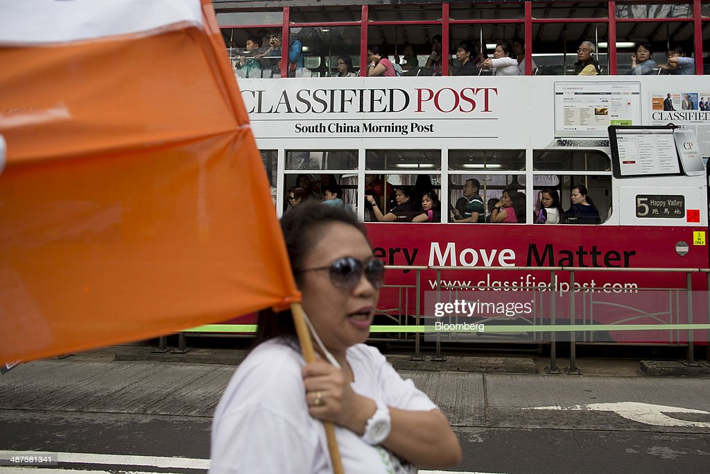 People in a tram watch a women carry a banner during a labor day rally in Hong Kong, China, on Thursday, May 1, 2014. Thousands of people have marked labor day by staging a series of rallies to demand better workers' rights. Photographer: Brent Lewin/Bloomberg via Getty Images