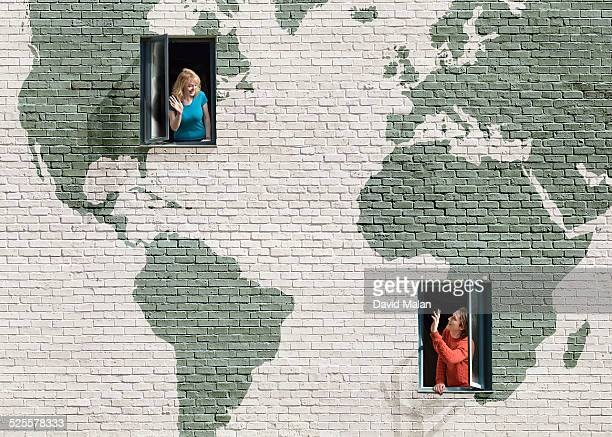 2 people in a windowed wall with a world map