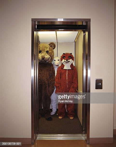 People in animal costumes riding elevator