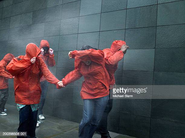 People in anoraks struggling against rainstorm, shielding faces