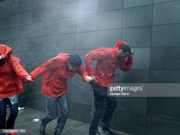 People in anoraks struggling to walk against rainstorm