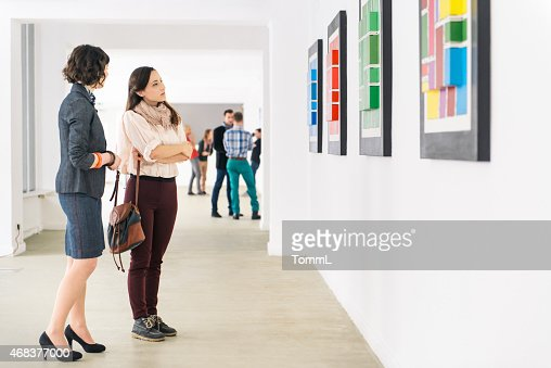 People In Art Gallery Looking At Artwork