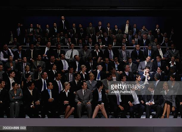 People in auditorium looking at man on mobile phone(digital composite)