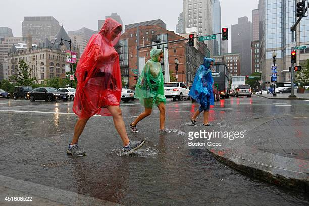People in brightly colored ponchos walk through the rain in Boston on July 4 2014